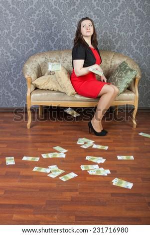 sexy girl sitting under euros rain - stock photo