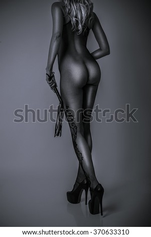 sexy girl slim body in fetish lace lingerie and leather whip - stock photo