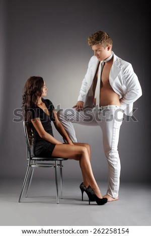 Sexy girl stares at elegant half-naked stripper - stock photo