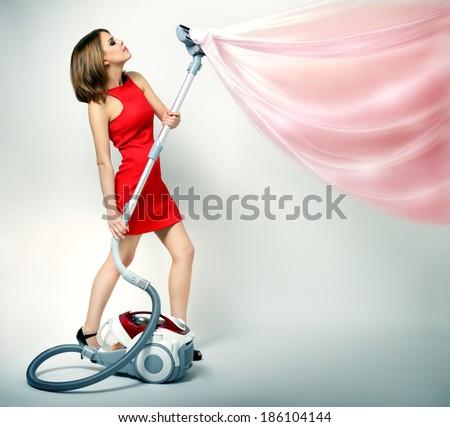 Sexy girl using vacuum cleaner. light background - stock photo