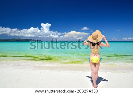 Sexy girl wearing a straw hat on the tropical beach enjoying summer holidays
