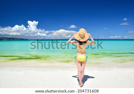Sexy girl wearing a straw hat standing on the tropical beach enjoying the summer holidays travel - stock photo