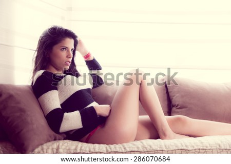 sexy girl wearing panties and striped sweater sitting in sofa with worried facial expression