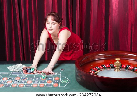 sexy girl wearing red dress takes a bit stake - stock photo
