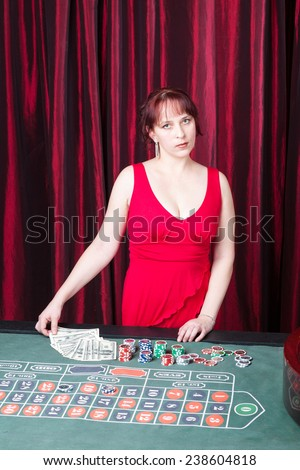 sexy girl wearing red dress with dollars in a casino - stock photo