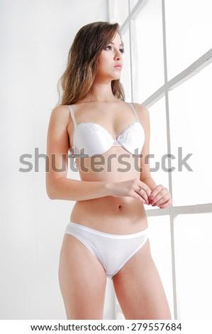 sexy girl wearing white lingerie posing near door  - stock photo