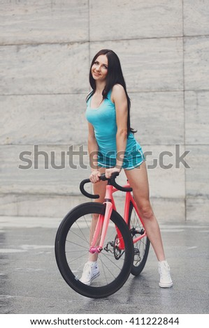 Sexy girl with bicycle. Young slim sexy sportive woman in blue shorts and white snickers long-haired, sensual posing with pink fix bicycle in urban city enviroment. Soft toned.  - stock photo