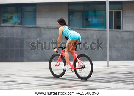 Sexy girl with bicycle. Young slim sexy sporty woman in blue shorts and white snickers long-haired, sensual posing with pink fix bicycle in urban city environment. Soft toned. Shaped buttocks. - stock photo