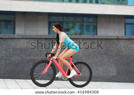 Sexy girl with bicycle. Young slim sexy sporty woman in blue shorts and white snickers long-haired, sensual riding at pink fix bicycle in urban city environment. Soft toned.