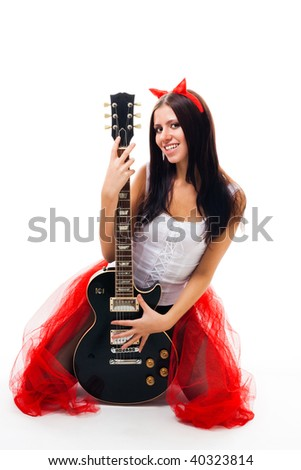 Sexy girl with black guitar and horns,stand on her knees, smile, isolated on white