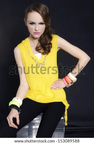 Sexy girl with bright make-up sitting cube on black background - stock photo