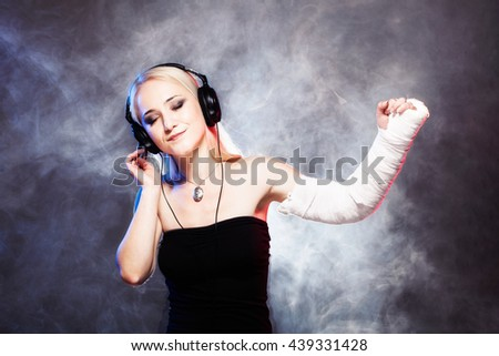 sexy girl with broken arm listening music on headphones and dancing, disco smoke in the background