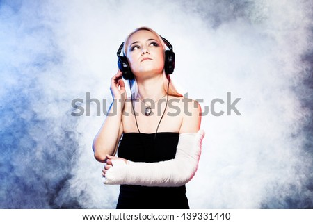 sexy girl with broken arm listening music on headphones and dancing, disco smoke in the background - stock photo