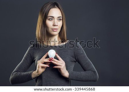 sexy girl with brunette hair in grey dress posing in studio. Perfect hairdo and skin. holding the lamp, as a sign appeared a good idea - stock photo