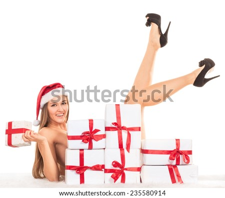 sexy girl with Christmas gifts lying on the carpet, smiling and looking at the camera - stock photo