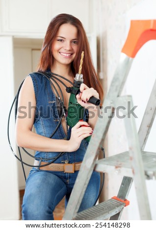 Sexy girl with drill on stepladder in interior - stock photo