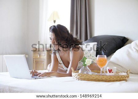sexy girl with her laptop in her bedroom