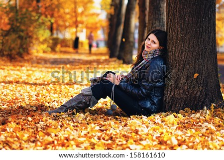 Sexy girl with long hair sitting on the ground full of fallen golden and red leaves during autumn time leaning against a tree wearing jeans, jacket, high boots and scarf smiling