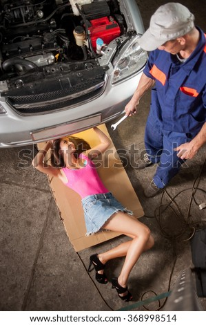 Sexy girl with long legs lying under car checking the engine and auto mechanic standing near her giving her tools at the car repair shop. Girl wearing high heels blue jeans skirt. View from the top.