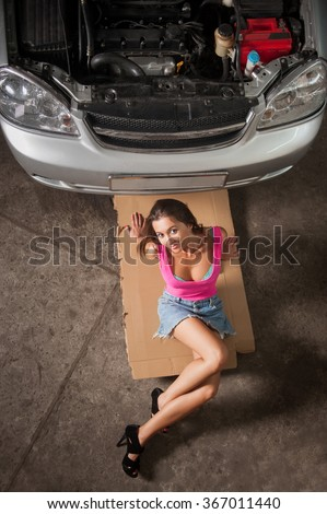 Sexy girl with long legs sitting near car at the car repair shop. Wearing high heels blue jeans skirt and pink top. View from the top - stock photo