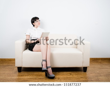 Sexy girl with secretary look sit on a coach