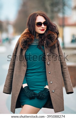 sexy glamorous brunette girl, beautiful young woman with chic long dark hair, wearing stylish sunglasses, trendy green dress by elegant coats with fluffy fur and gloves outdoor, trendy makeup - stock photo