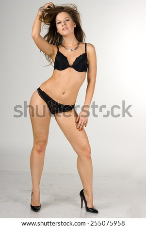 Sexy glamorous girl in black swimsuit isolated on white background