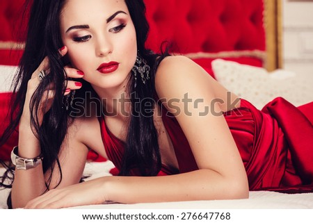 sexy glamour woman with black hair in elegant red dress in luxury bedroom