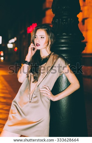 Sexy gorgeous brunette girl portrait in night city lights. Motion effect.