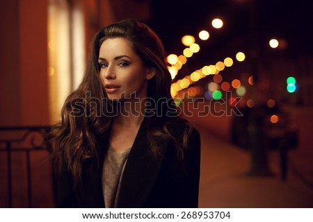 Sexy gorgeous brunette girl portrait in night city lights. Vogue fashion style portrait of young pretty beautiful woman with long dark curly hair. Shallow DOF - stock photo