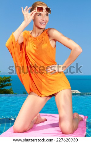 Sexy gorgeous woman posing poolside kneeling on a towel in a short orange top lifting her sunglasses with a happy smile as she looks to the side  infinity pool overlooking the ocean - stock photo