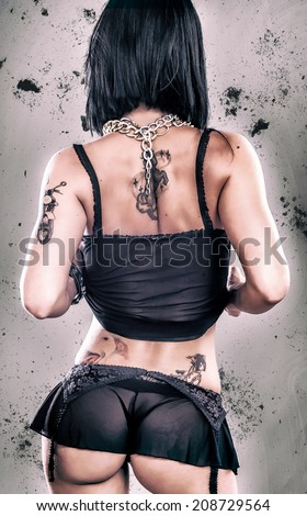 Sexy Grunge Tattoo Girl. Beautiful and erotic lady with tattoo. Studio shoot. Rear View.