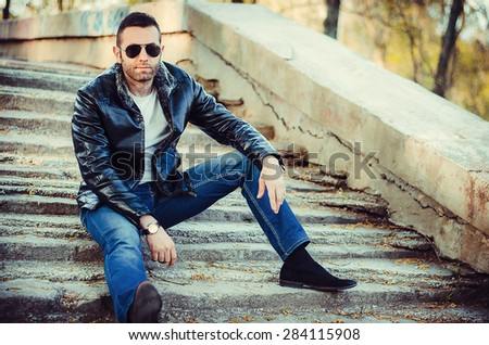 Sexy guy with attitude wearing leather jacket and sunglasses outdoors - stock photo