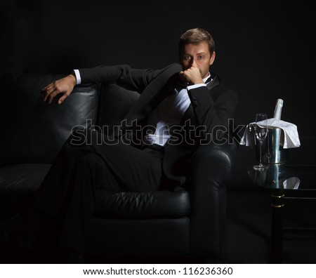 Sexy handsome man in tuxedo sitting in the darkness of a nightclub with an unopened bottle of champagne on ice waiting for his date