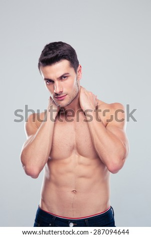 Sexy handsome man posing over gray background and looking at camera - stock photo