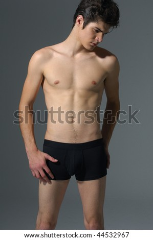 sexy handsome muscular young man on gray background - stock photo