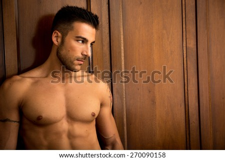 Sexy handsome young man standing shirtless in his bedroom against wooden wardrobe door - stock photo