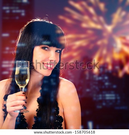Sexy happy woman with champagne glass over fireworks background - stock photo