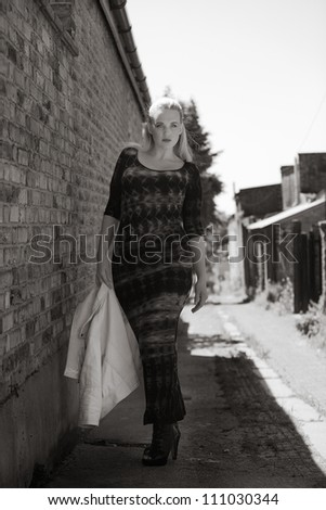 sexy high fashion shot of woman standing in a side street