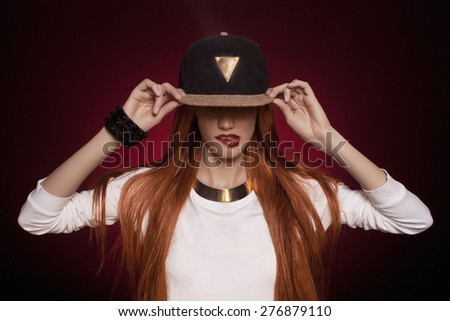 Sexy hip-hop woman in cap with long red hair. Fashion portrait of modern girl in cap - stock photo