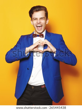 Sexy hipster boy in the jacket in the studio make hands heart