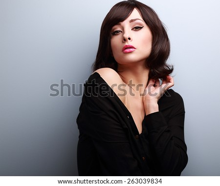 Sexy hot makeup woman with short hairstyle posing in black shirt on blue background with empty copy space - stock photo