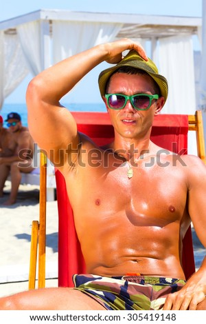 Sexy hot muscular Man on beach looking to camera smiling ,wearing hipster hat, sunglasses,military printed trousers.Young male model enjoying summer travel holiday by the ocean on luxury beach resort - stock photo