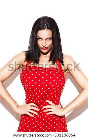 Sexy housewife in red dotted apron posing - stock photo
