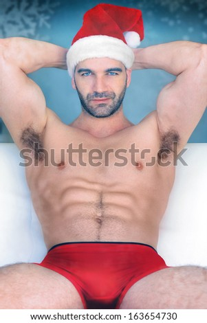 Sexy hunk Santa in red underwear and cap sitting against winter background