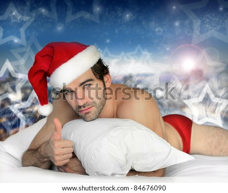 Sexy hunky male model santa laying in bed with magical winter background - stock photo