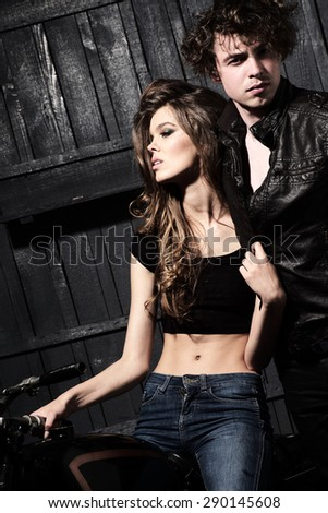Sexy impassioned young couple in garage interior on wooden wall background, vertical picture - stock photo