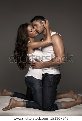 Sexy kissing couple in bed - stock photo