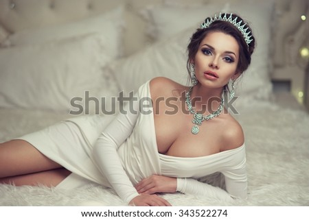 Sexy lady in evening dress with decollete and jewelry with diamonds lying on bed. Fashion style portrait of young beautiful rich woman