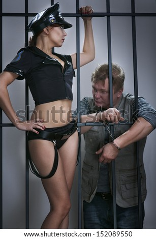 sexy lady police officer guards the offender in prison - stock photo